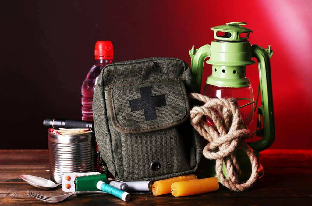 a survival kit with water, rope, lamp, knife, flares